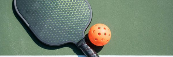 Pickle ball and paddle on court