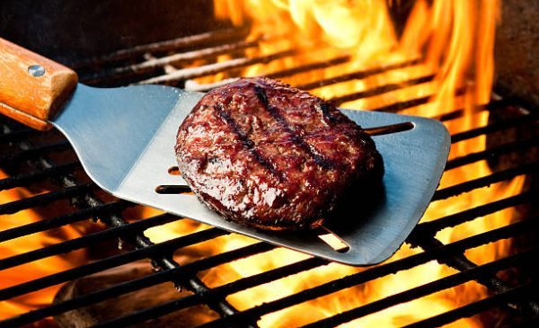 Juicy burger with appetizing grill marks on a silver spatula over a flaming charcoal barbecue grill